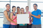 Portrait of a group of fitness class holding blank paper — Stock Photo