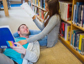 Romantic couple with books at the library aisle — Stock Photo