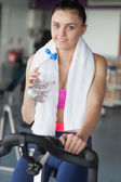 Tired woman drinking water while working out at spinning class — Stock Photo