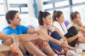 Side view of a group of fitness class sitting in row — Stock Photo