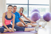 Fitness class and instructor sitting on exercise mats — Stock Photo