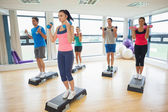 Instructor with fitness class performing step aerobics exercise with dumbbells — Stok fotoğraf