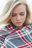 Close up of a young woman covered with blanket — Stock Photo