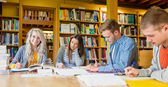 Group of students writing notes at library desk — Stock Photo