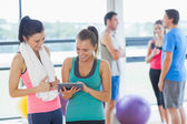 Fit women looking at digital table with friends chatting in background — Stock Photo