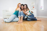 Happy young female friends embracing on floor at home — Stock Photo