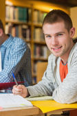 Portret van een glimlachende mannelijke student op bibliotheek bureau — Stockfoto