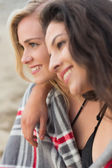 Two young women covered with blanket at beach — Stock Photo