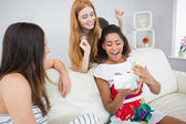 Cheerful young women surprising friend with a gift — Stock Photo