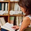 Young female student studying in library — Vídeo de stock
