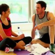 Stock Video: Two sporty friends sitting on floor in fitness hall