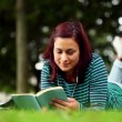 Pretty student lying on grass reading a book listening to music — Stock Video
