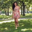 Stock Video: Gorgeous happy brunette walking in park