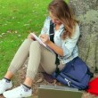 Student studying and leaning against a tree — Stock Video