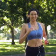 Stock Video: Happy brunette running in park