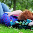 Pretty young student lying on the grass on her bookbag — Stock Video