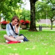 Happy student sitting on the grass making a phone call — Stock Video
