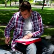 Young student studying on the bench outside — Video