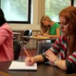 Stock Video: Concentrating students sitting in class and taking notes