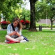 Student sitting on the grass making a phone call — Stock Video