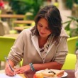 Smiling student studying while having lunch in canteen — Video Stock