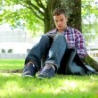 Young student sitting on the grass using tablet pc — Stock Video