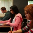 Stock Video: Attentive students sitting in classroom and taking notes