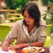 Pretty student studying while having lunch in canteen — Video Stock