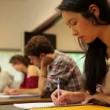 Stock Video: Attentive students sitting an exam in a classroom