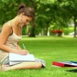 Stockvideo: Pretty student writing outside