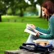 Student sitting on bench reading a book listening to music — Stock Video