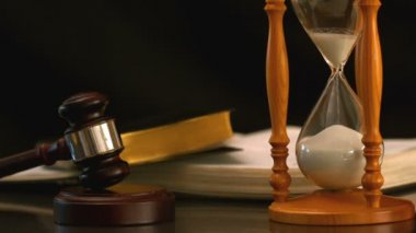 Sand flowing through hourglass beside gavel and bible — Stock Video