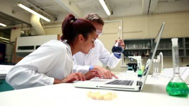 Attentive science students examining chemical and using laptop — Stock Video