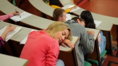 Student asleep at desk in lecture hall — Stock Video