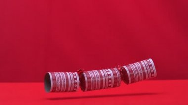 Christmas cracker falling and bouncing on red background — Stock Video
