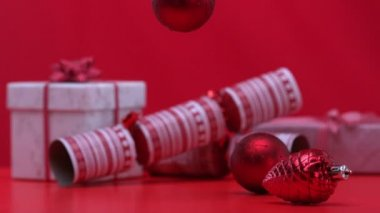 Christmas decorations spinning and falling beside crackers and presents — Stock Video