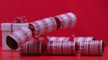 Christmas cracker dropping and bouncing beside present on red background — Stock Video