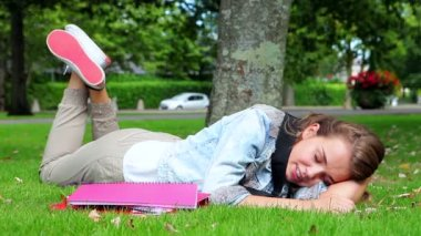 Happy student lying on the grass and answering her phone — Stock Video