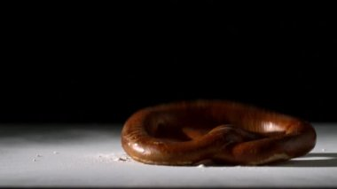 Pretzel falling onto flour on black background — Stock Video