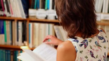 Young female student reading in library — Stock Video