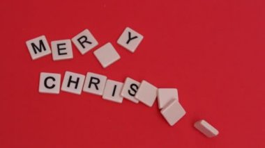Letter tiles moving to spell out merry christmas on red background — Stock Video