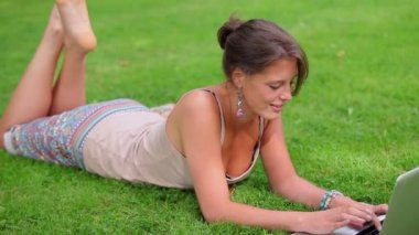 Happy student lying on grass using her laptop — Stock Video