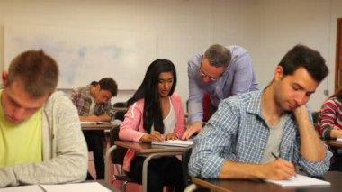Teacher explaining something to student in class — Stock Video