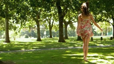 Attractive brunette bouncing through park — Stock Video