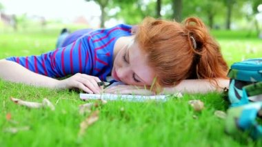 Pretty young student lying on the grass asleep — Stock Video