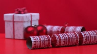 Christmas cracker dropping and bouncing beside present and decorations — Stock Video