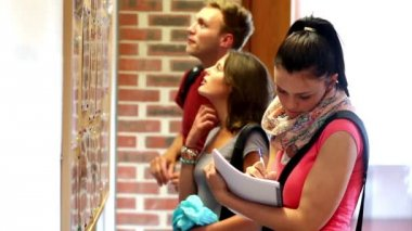 Students checking the notice board — Vídeo de stock