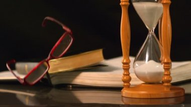 Reading glasses falling beside hourglass and bible — Stock Video