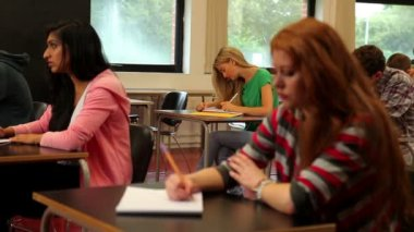 Concentrating students sitting in class and taking notes — Stock Video