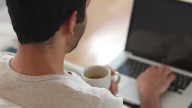 Man drinking coffee while using laptop — Stock Video